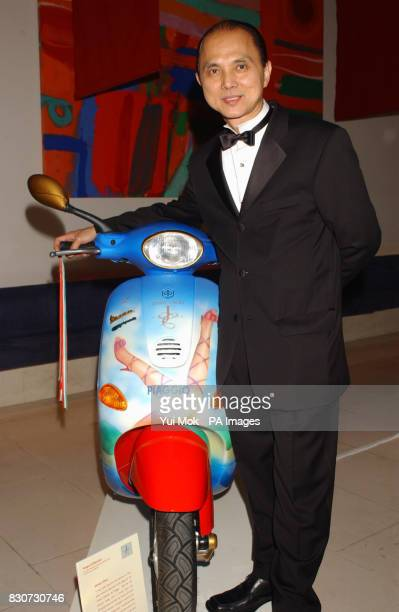 Shoe designer Jimmy Choo standing next to the bike he designed attending an auction of specially commissioned Vespa scooters in aid of Action on...