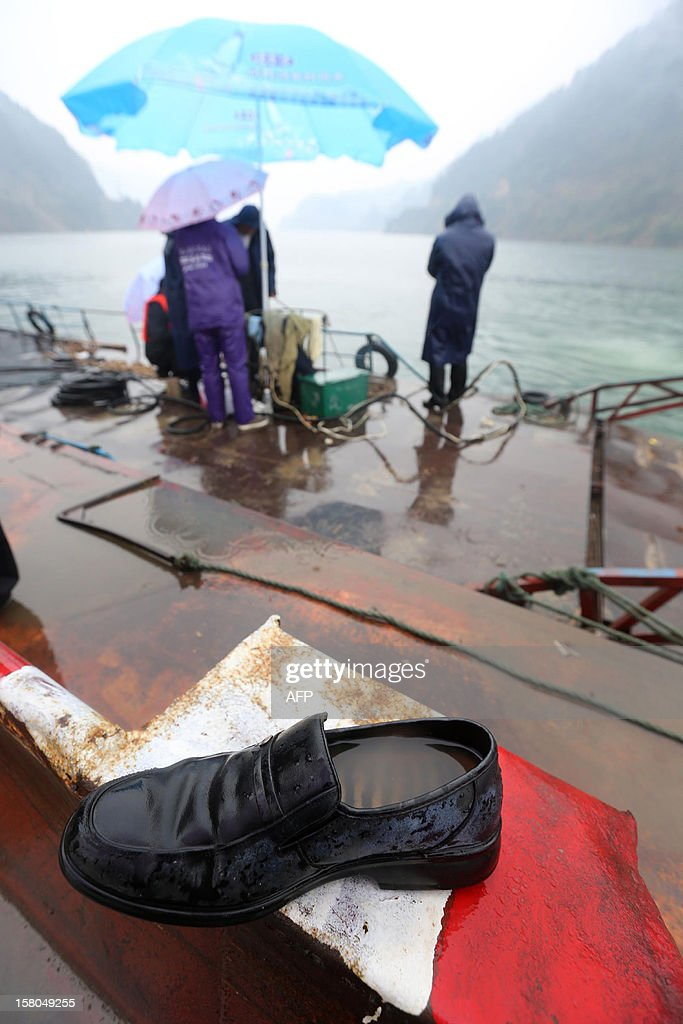 A shoe fished from the water lies on the deck of a rescue vessel after a flat-bottomed cargo boat capsized in waters near Pingshan village in Anhua county, central China's Hunan province on December 10, 2012. Eight people have been confirmed missing after the accident on December 9. Four trucks that the boat was transporting went down with the boat local authorities said. CHINA