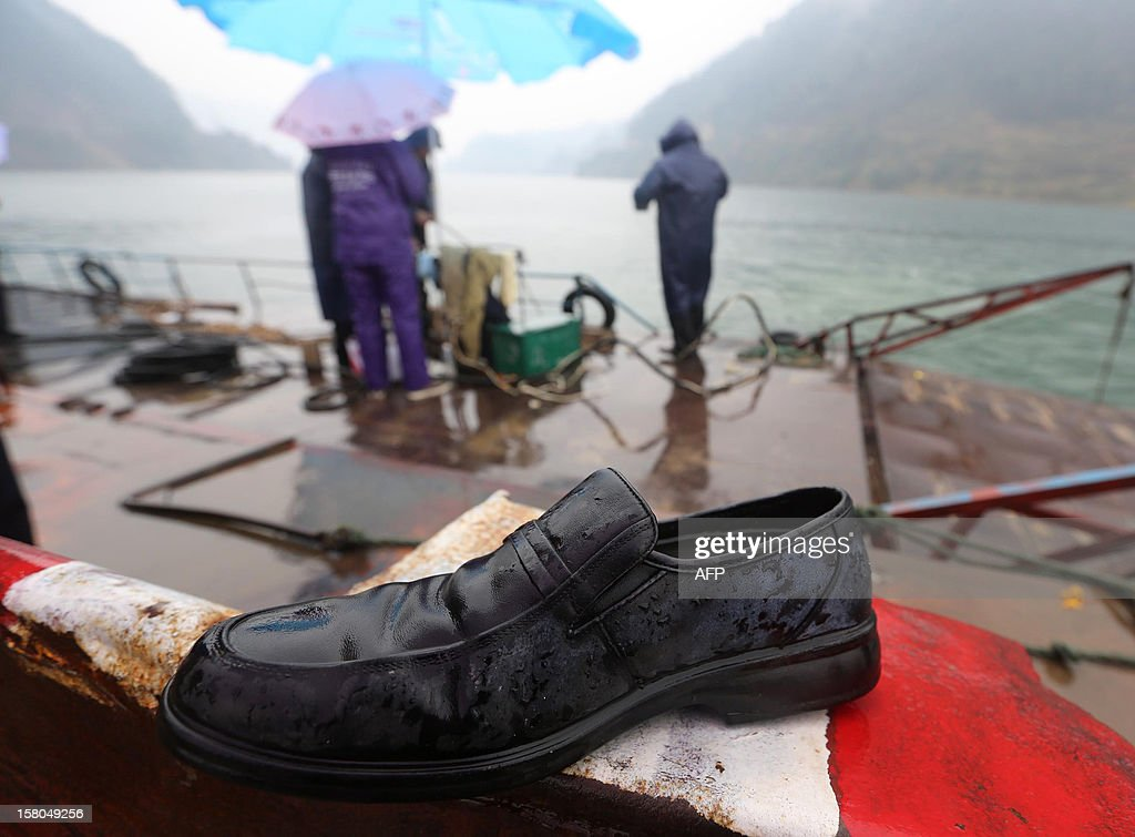 A shoe fished from the water lies on the deck of a rescue vessel after a flat-bottomed cargo boat capsized in waters near Pingshan village in Anhua county, central China's Hunan province on December 10, 2012. Eight people have been confirmed missing after the accident on December 9. Four trucks that the boat was transporting went down with the boat local authorities said. CHINA OUT AFP PHOTO