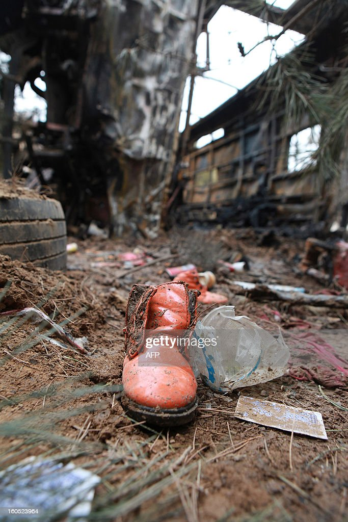 A shoe lies on the ground after a bus plunged off a road and down a hill, catching fire after the impact, in Ningxian, northwest China's Gansu province on February 2, 2013. The accident took the lives of 18 people. CHINA OUT AFP PHOTO