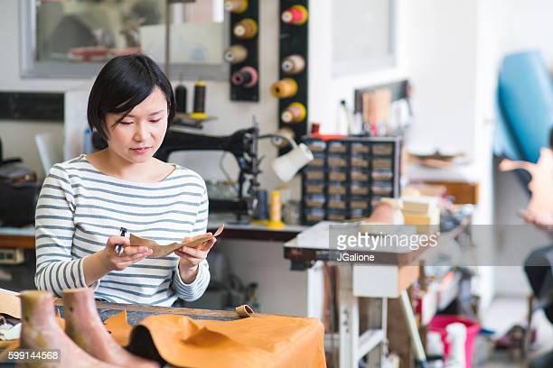 Shoe maker holding fresh cut leather