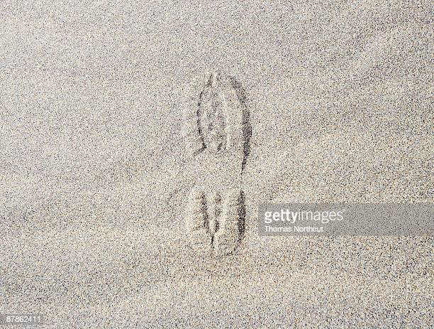 Shoe print in sand.