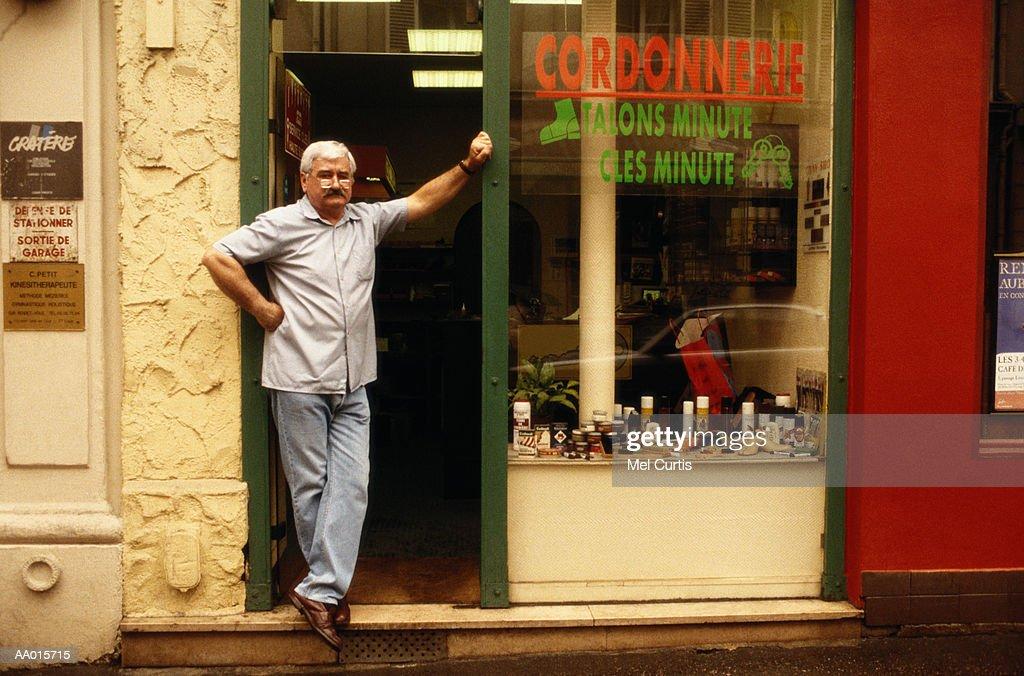 Shoe Repair Man  in the Doorway of His Shop