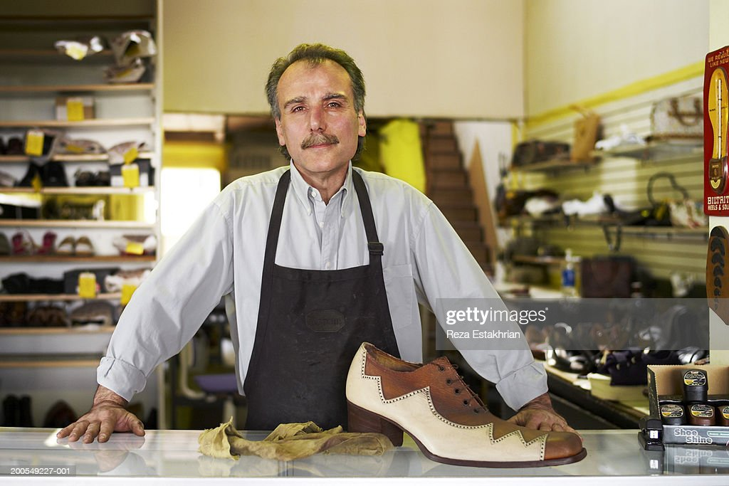 Shoe repair man with giant shoe on counter