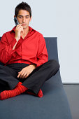 Shoeless businessman sitting on chaise and using cell phone