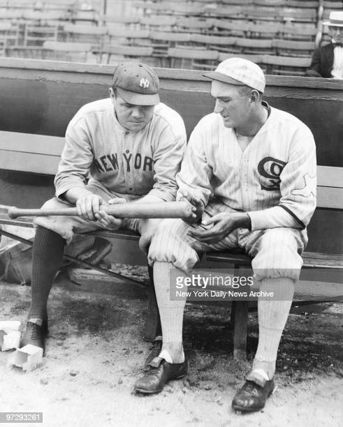 Shoeless Joe Jackson of the Chicago White Sox and the New York Yankees' Babe Ruth look at one of Babe's home run bats