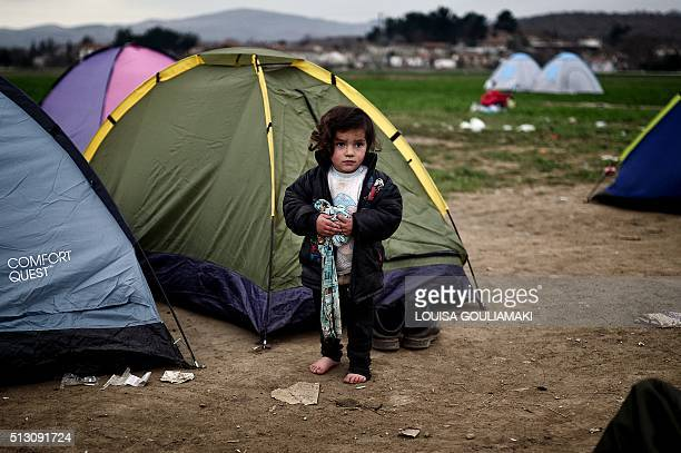 A shoeless migrant girl stands at the makeshift refugee camp at the Greek Macedonian border near the Greek village of Idomeni on February 29 2016 A...