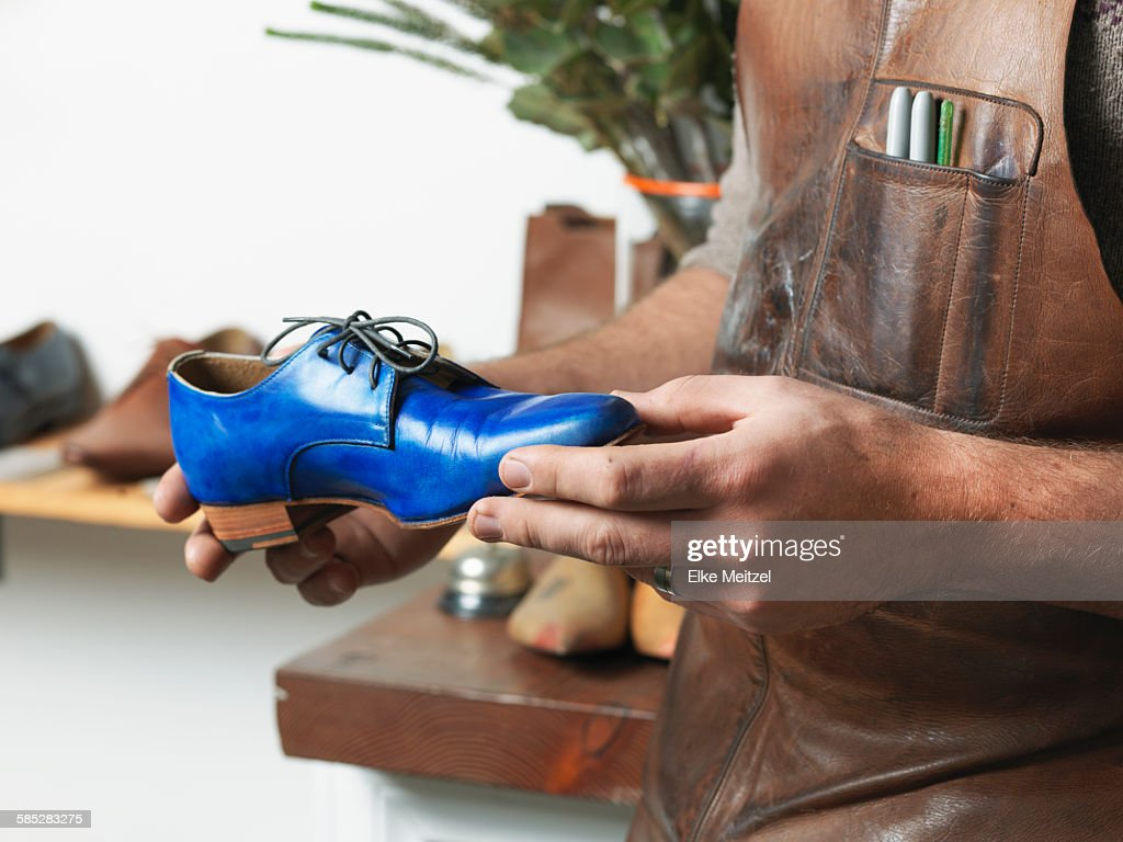 Shoemaker holding blue shoe in workshop