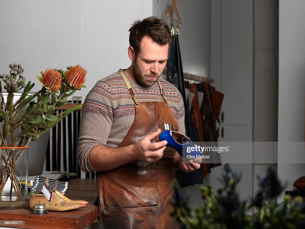 Shoemaker holding blue shoe in workshop