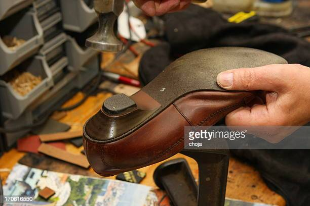Shoemaker in his workshop repairing shoe
