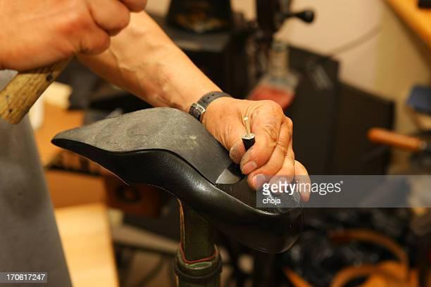 Shoemaker in his workshop repairing shoe