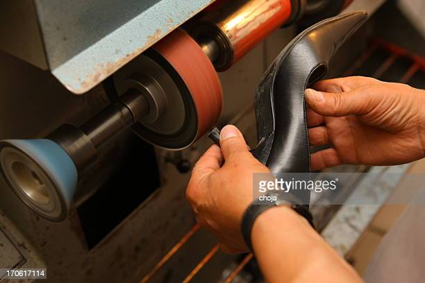 Shoemaker polishing sole of shoe