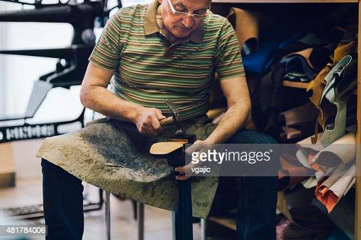Shoemaker putting sole on shoe.