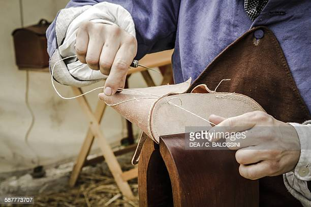 Shoemaker sewing the sole of a pair of shoes end of the 18th century Historical reenactment