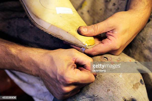 A shoemaker uses a blade to trim the leather sole of a luxury shoe in the Corthay workshop located beneath the company's store in Paris France on...