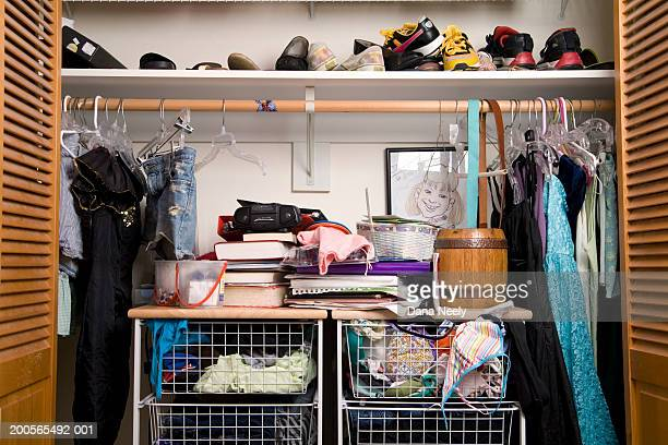 Shoes and clothes in closet, close-up