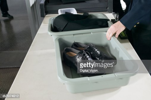 Shoes and Clothes in Containers on a table at Airport Customs