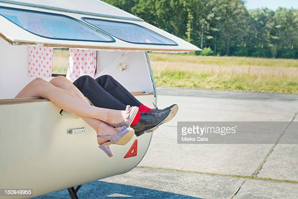 Shoes and legs of a newlywed couple in a caravan