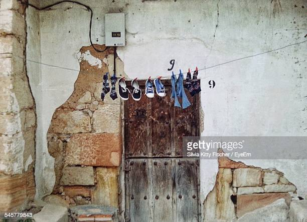 Shoes And Socks Hanging On Rope In Front Of Abandoned House