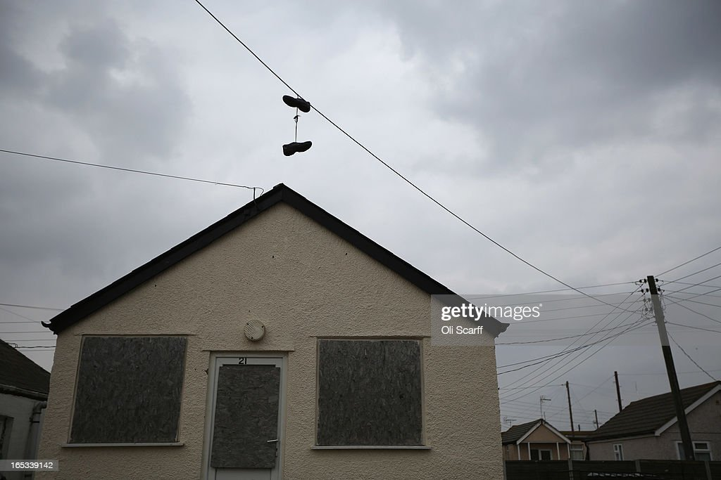 Shoes hang from telephone wires in front of dilapidated properties in the seaside town of East Jaywick, the most deprived place in England, on April 3, 2013 in Jaywick, England. The Government's 2011 Indices of Multiple Deprivation' measure ranks Jaywick as the most deprived of all 32,482 small wards in England and Wales. The area also has the greatest number of young people not in employment, education or training; one third of 16 to 24 year-olds claim Jobseeker's Allowance, compared to the national average of 6 per cent. Changes to the benefits and tax system which came into force on April 1, 2013 have included a cut in housing benefit payments for working-age social housing tenants whose property is deemed larger than they need and council tax support payments now being administered locally.