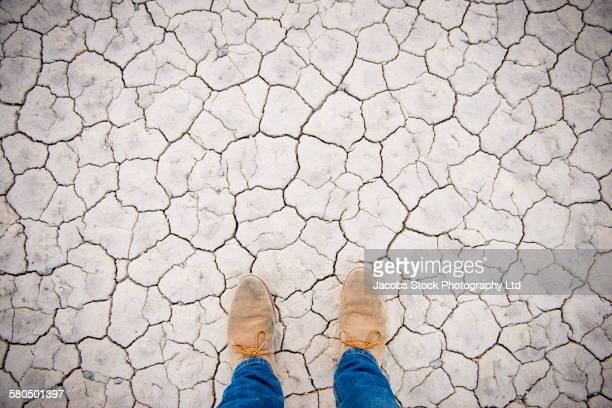 Shoes of Caucasian man on cracked desert ground