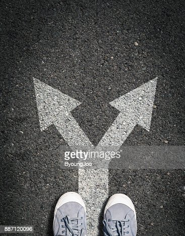 shoes on asphalt road with two directions sign, concept is making choice and makin decsion : Stock Photo