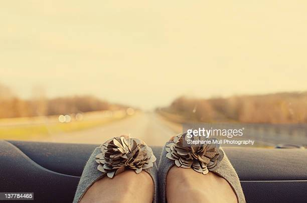 Shoes on dashboard of car