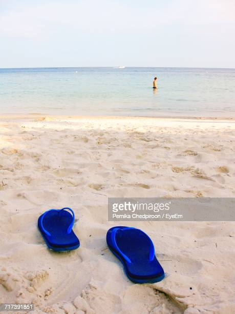 Shoes On Sand At Beach Against Clear Sky
