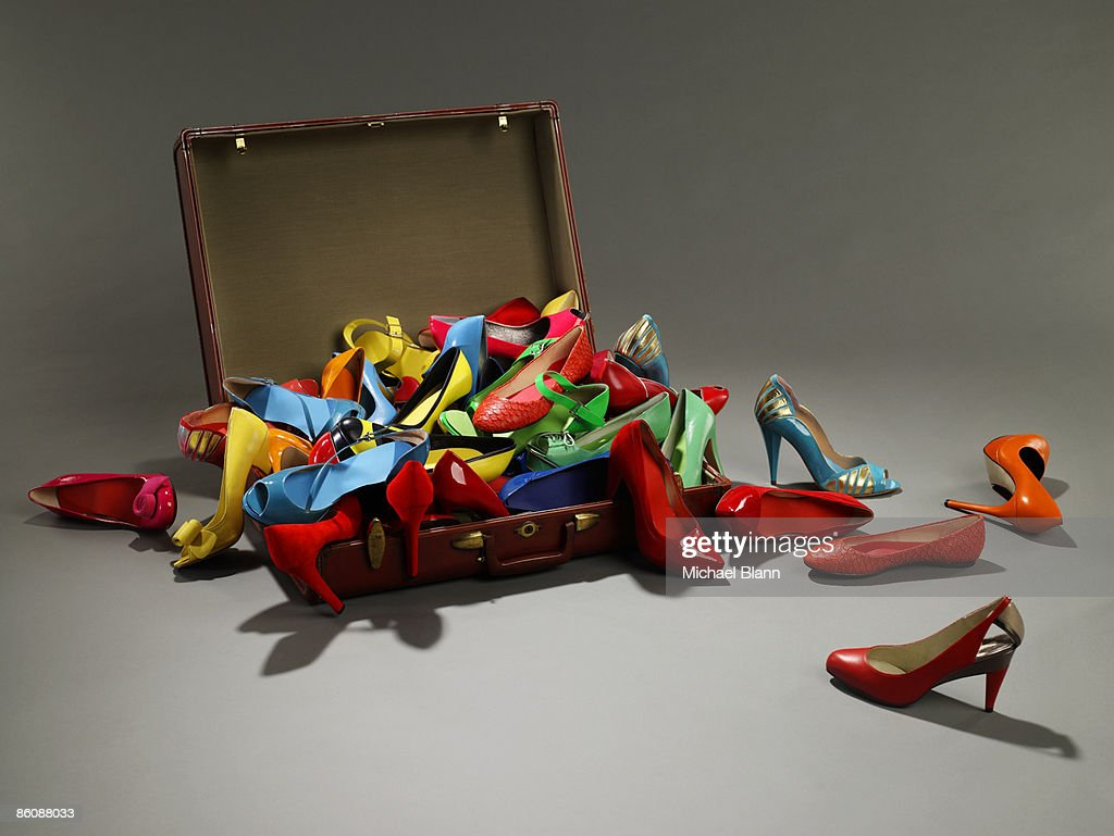 Shoes overflow from suitcase : Stock Photo