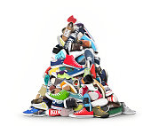 A very large pile of athletic shoes on white background