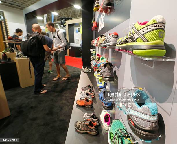 Shoes sits on display as sellers and buyers look over gear at the Salomon booth during the Outdoor Retailer Summer Show at the Salt Palace in Salt...