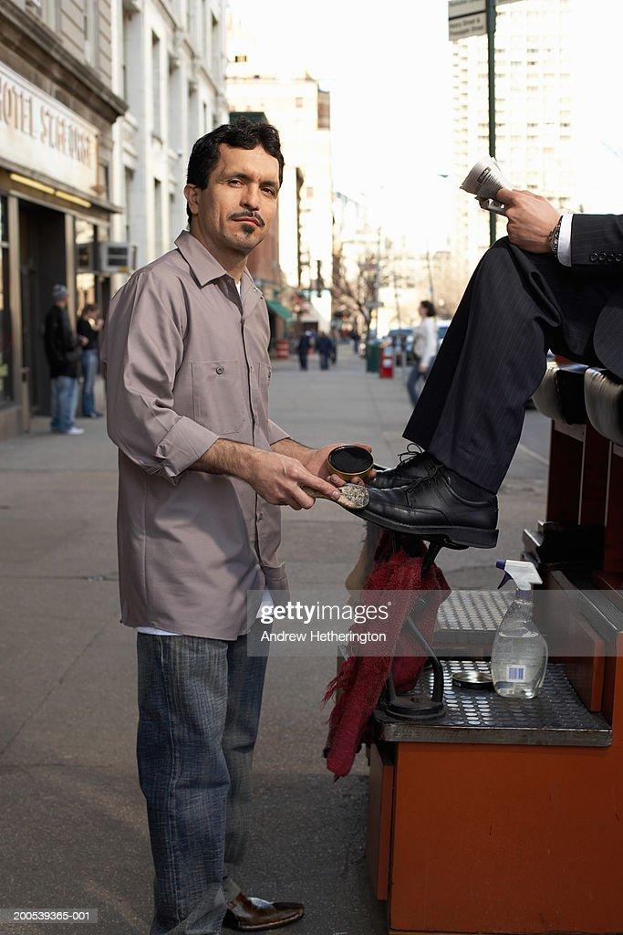 Shoeshine man with customer on sidewalk, portrait : Stock Photo