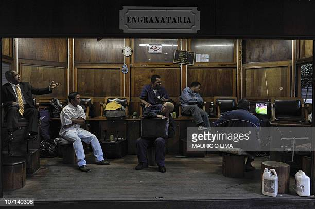 Shoeshiners watch on a TV the second half time of the FIFA World Cup South Africa 2010 Group G football match between Brazil and North Korea at a...