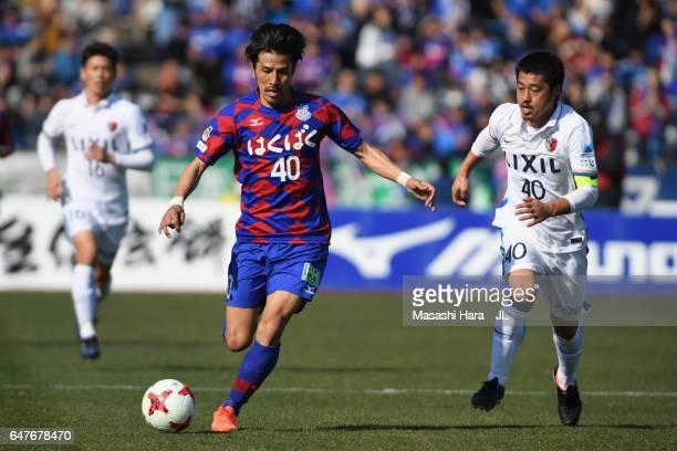 Shohei Ogura of Ventforet Kofu and Mitsuo Ogasawara of Kashima Antlers compete for the ball during the JLeague J1 match between Ventforet Kofu and...