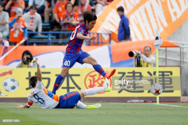 Shohei Ogura of Ventforet Kofu is tackled by Kei Koizumi of Albirex Niigata during the JLeague J1 match between Ventforet Kofu and Albirex Niigata at...