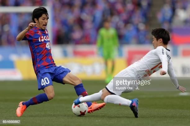 Shohei Ogura of Ventforet Kofu is tackled by Keisuke Oyama of Omiya Ardija during the JLeague J1 match between Ventforet Kofu and Omiya Ardija at...