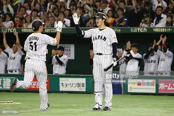 Shohei Ohtani of Japan celebrates with pinch runner Seiya Suzuki in the fifth inning during the international friendly match between Japan and...