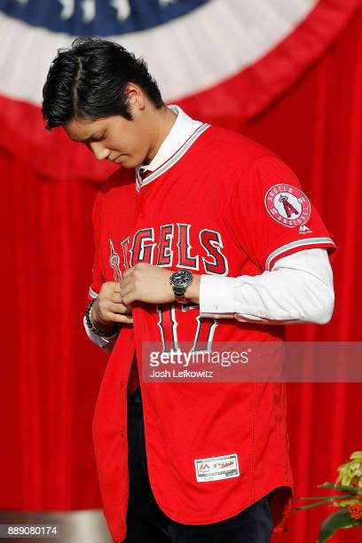 Shohei Ohtani puts on his jersey for the first time during his introduction to the Los Angeles Angels of Anaheim at Angel Stadium of Anaheim on...