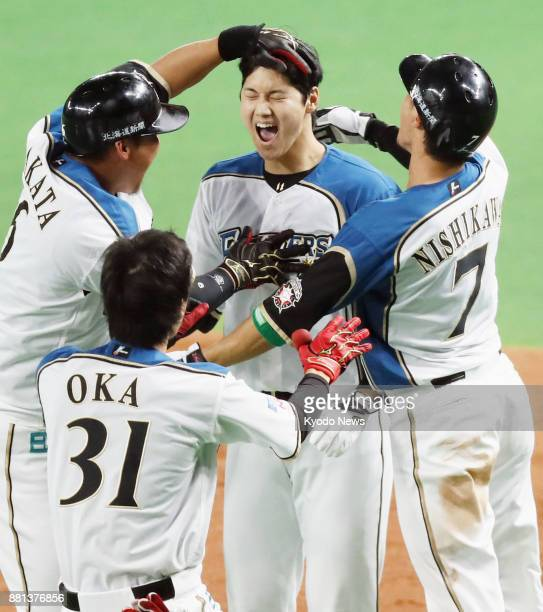 Shohei Otani of the Nippon Ham Fighters is congratulated by teammates after hitting a walkoff single to beat the Hiroshima Carp in Game 3 of the...