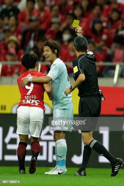 Shohei Takahashi of Jubilo Iwata is shown a yellow card by referee Itaru Hirose after fouling on Yuki Muto of Urawa Red Diamonds during the JLeague...