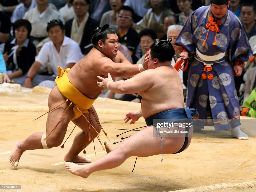Shohozan (L) pushes out Goeido out of the ring to win during day five of the Grand Sumo Nagoya Tournament at Aichi Prefecture Gymnasium on July 11, 2013 in Nagoya, Aichi, Japan.