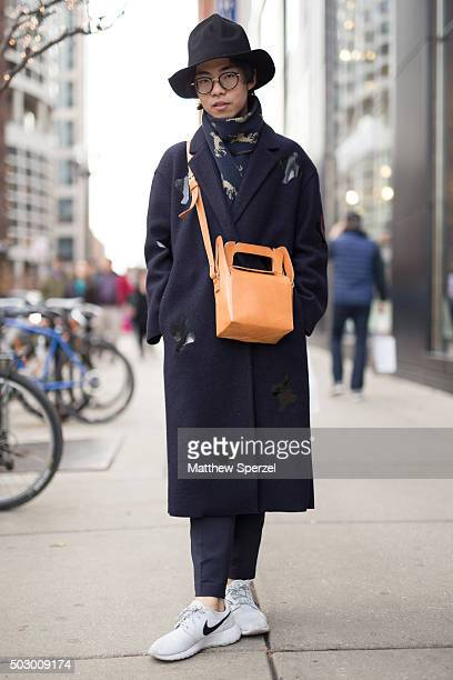 Shoka Xu is seen on Michigan Avenue wearing a black HM hat dark blue patterned wool COS coat blue patterned Topshop scarf tan leather MM6 bag dark...