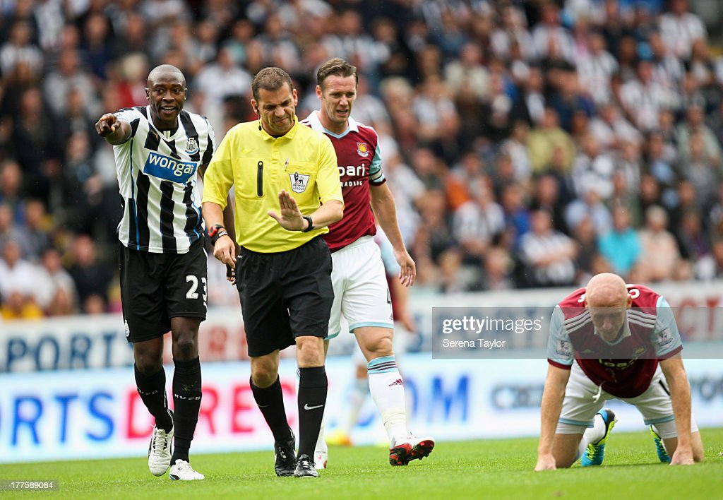 Shola Ameobi (L) argues with referee Phil Dowd during the Barclays Premiership Match against West Ham United at St. James Park on August 24, 2013, in Newcastle upon Tyne, England.