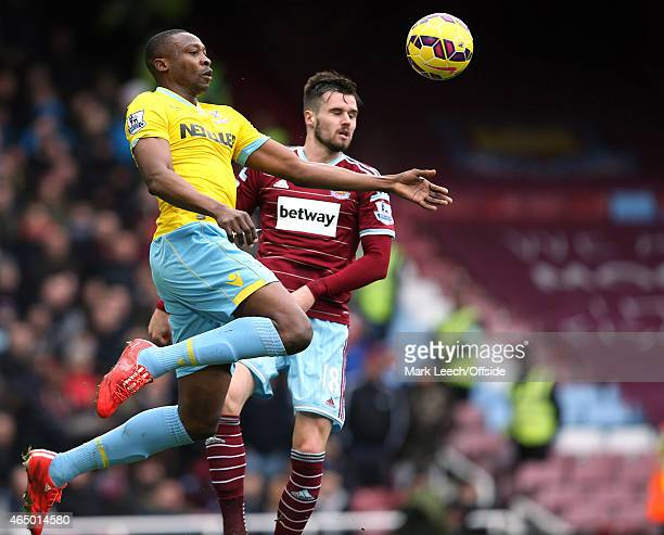 Shola Ameobi of Crystal Palace gets to the ball before Carl Jenkinson of West Ham during the Barclays Premier League match between West Ham United...
