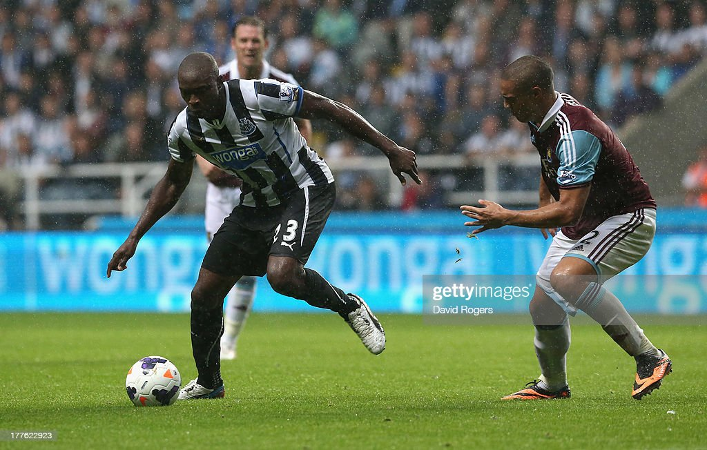 Shola Ameobi of Newcastle moves away from Winston Reid during the Barclays Premier League match between Newcastle United and West Ham United at St James' Park on August 24, 2013 in Newcastle upon Tyne, England.