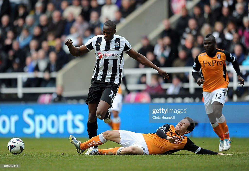 Shola Ameobi (L) of Newcastle United is tackled by Sascha Riether of Fulham during the Barclays Premier League match between Newcastle United and Fulham at St James' Park on April 7, 2013 in Newcastle upon Tyne, England.