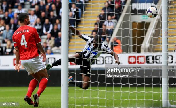 Shola Ameobi of Newcastle United scores their first goal with a header as Steven Caulker of Cardiff City looks on during the Barclays Premier League...