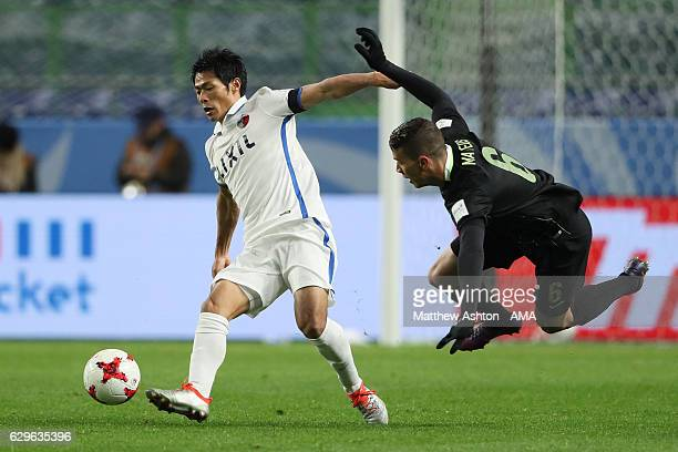 Shoma Doi of Kashima Antlers competes wth Mateus Uribe of Atletico Nacional during the FIFA Club World Cup Semi Final match between Atletico Nacional...