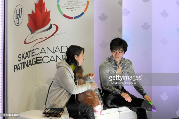 Shoma Uno of Japan waits for his score with his coach Mihoko Higuchi at the kiss and cry after competing in the Men's Singles Short Program during...
