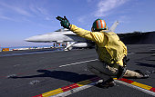 A shooter signals the launch of an F/A-18 Super Hornet.